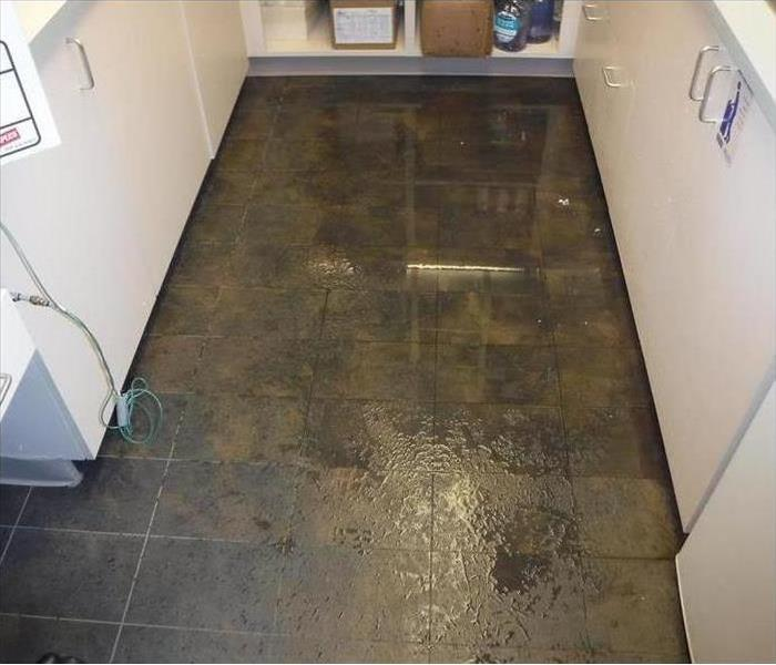 flooded brown floor with white cabinets on side
